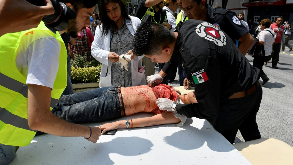 A woman is assisted after being injured during a quake in Mexico City on September 19, 2017. A powerful earthquake shook Mexico City on Tuesday, causing panic among the megalopolis' 20 million inhabitants on the 32nd anniversary of a devastating 1985 quake. The US Geological Survey put the quake's magnitude at 7.1 while Mexico's Seismological Institute said it measured 6.8 on its scale. The institute said the quake's epicenter was seven kilometers west of Chiautla de Tapia, in the neighboring state of Puebla. / AFP PHOTO / Omar TORRES (Photo credit should read OMAR TORRES/AFP/Getty Images)
