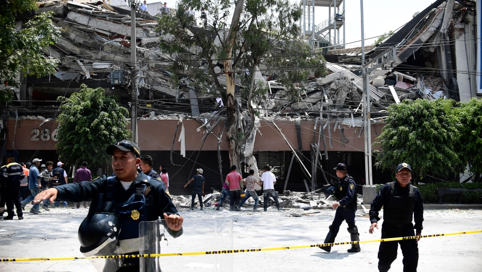 Police officers cordon the area off after a building collapsed during a quake in Mexico City on September 19, 2017. A powerful earthquake shook Mexico City on Tuesday, causing panic among the megalopolis' 20 million inhabitants on the 32nd anniversary of a devastating 1985 quake. The US Geological Survey put the quake's magnitude at 7.1 while Mexico's Seismological Institute said it measured 6.8 on its scale. The institute said the quake's epicenter was seven kilometers west of Chiautla de Tapia, in the neighboring state of Puebla. / AFP PHOTO / Ronaldo SCHEMIDT (Photo credit should read RONALDO SCHEMIDT/AFP/Getty Images)