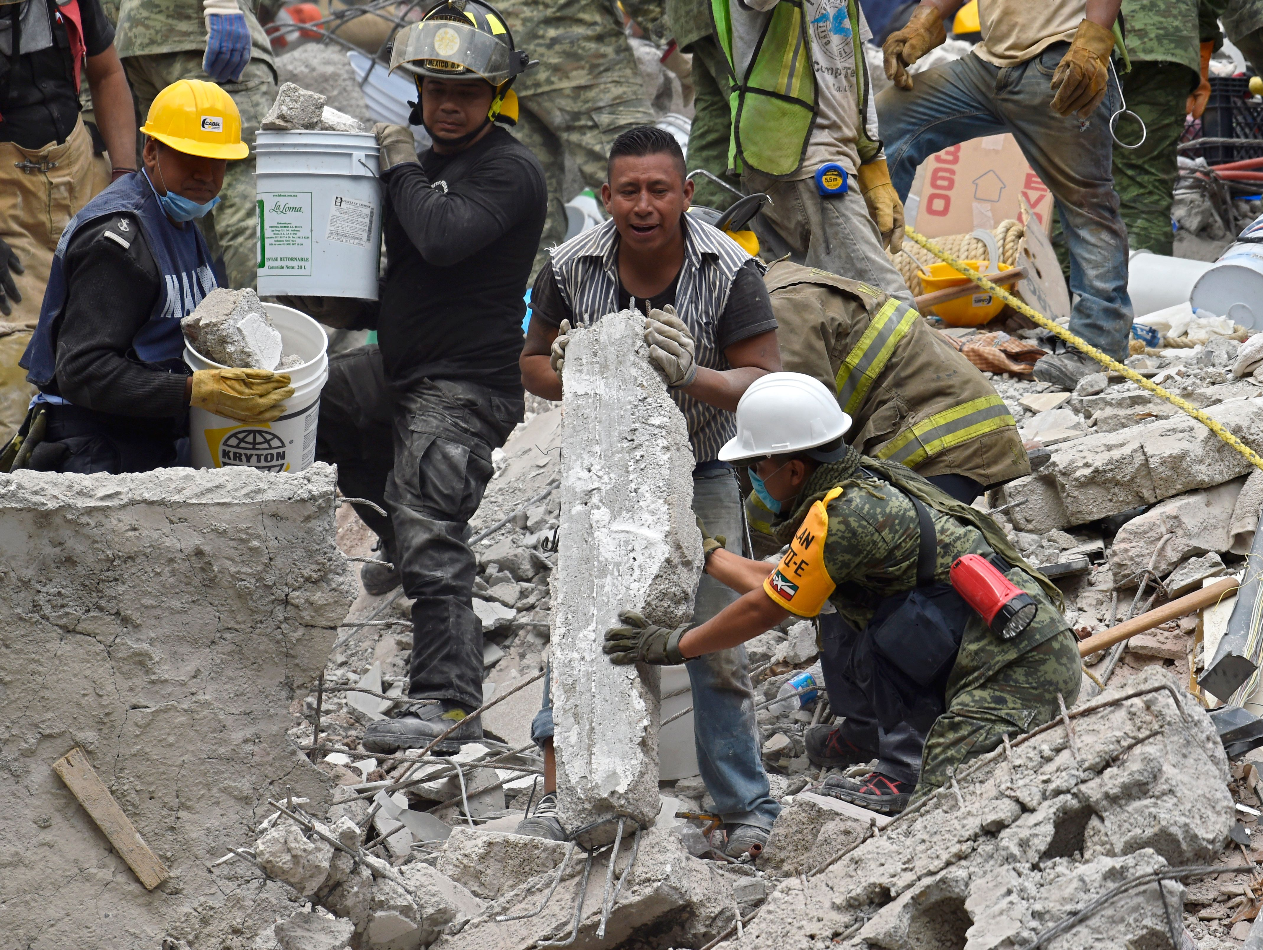 A marine, a firefighter, a volunteer and a soldier work together in the removal of debris of a flattened building in Mexico City on September 20, 2017 as the search for survivors continues a day after a strong quake hit central Mexico. A powerful 7.1 earthquake shook Mexico City on Tuesday, causing panic among the megalopolis' 20 million inhabitants on the 32nd anniversary of a devastating 1985 quake. / AFP PHOTO / Pedro PARDO (Photo credit should read PEDRO PARDO/AFP/Getty Images)