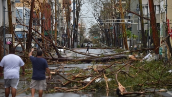 TOPSHOT - Men walk damaged trees after the passage of Hurricane Maria, in San Juan, Puerto Rico, on September 20, 2017. Maria slammed into Puerto Rico on, cutting power on most of the US territory as terrified residents hunkered down in the face of the island's worst storm in living memory. After leaving a deadly trail of destruction on a string of smaller Caribbean islands, Maria made landfall on Puerto Rico's southeast coast around daybreak, packing winds of around 150mph (240kph). / AFP PHOTO / HECTOR RETAMAL (Photo credit should read HECTOR RETAMAL/AFP/Getty Images)