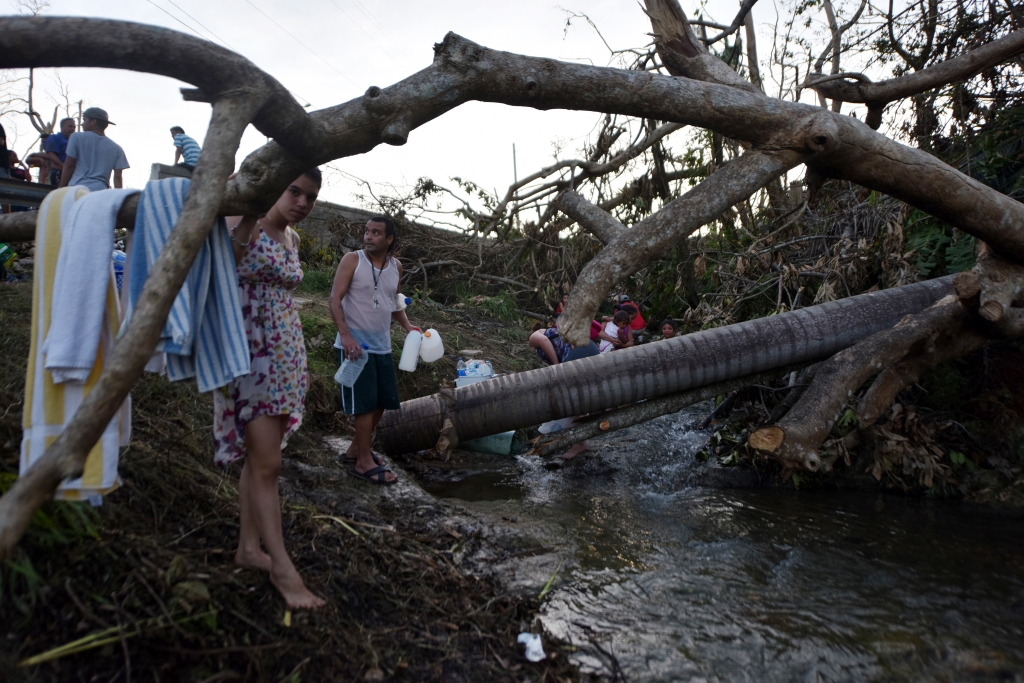 People carry water in bottles retrieved from a canal due to lack of water following passage of Hurricane Maria, in Toa Alta, Puerto Rico, on September 25, 2017. The US island territory, working without electricity, is struggling to dig out and clean up from its disastrous brush with the hurricane, blamed for at least 33 deaths across the Caribbean. / AFP PHOTO / HECTOR RETAMAL (Photo credit should read HECTOR RETAMAL/AFP/Getty Images)