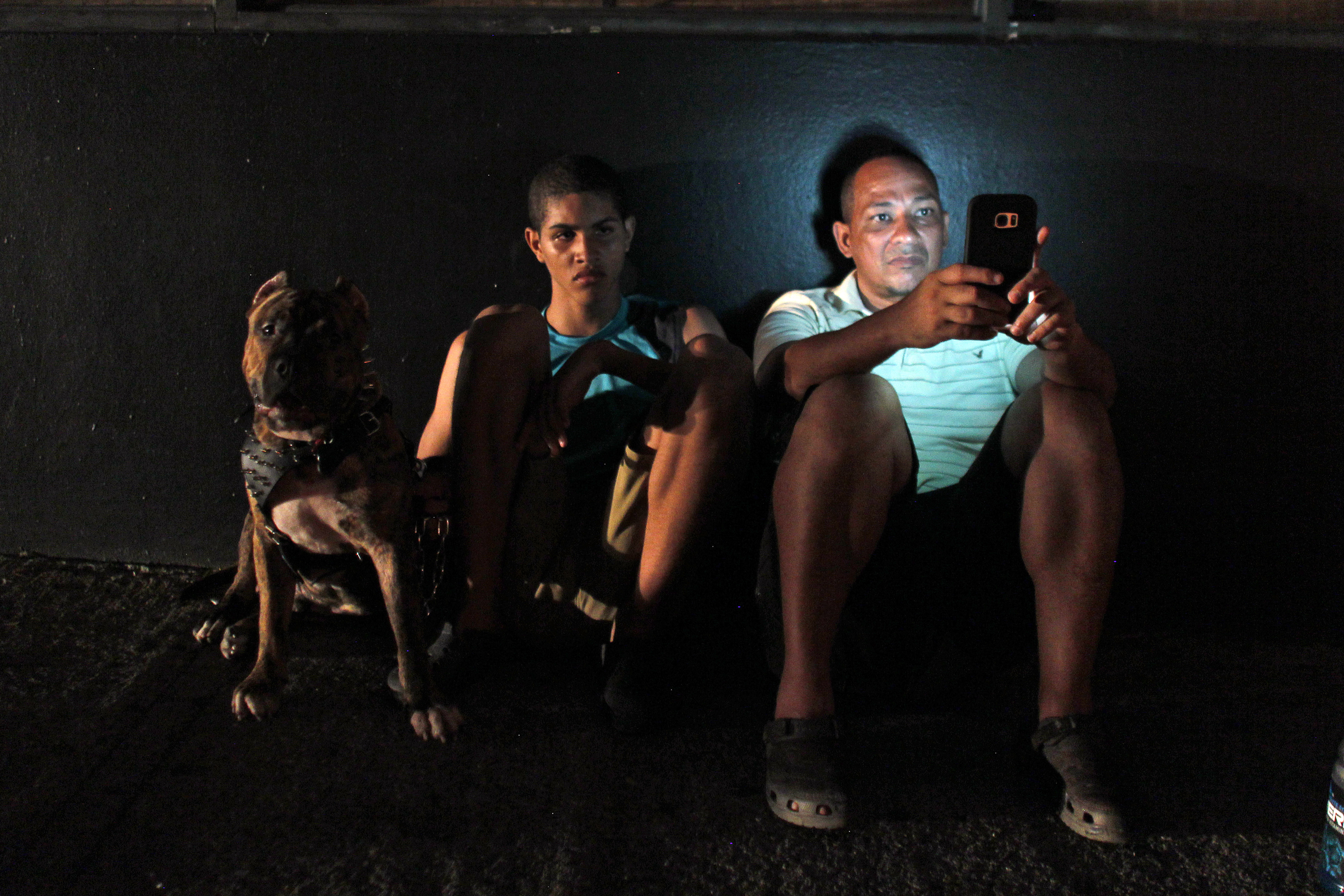 A man checks his cell phone next to a road at night in one of a few places with cell signal in San Juan, Puerto Rico, on September 25, 2017, where a 7pm-6am curfew has been imposed following impact of Hurricane Maria on the island. / AFP PHOTO / Ricardo ARDUENGO (Photo credit should read RICARDO ARDUENGO/AFP/Getty Images)