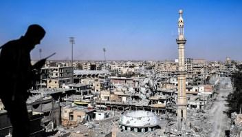 Un miembro de las Fuerzas Democráticas Sirias (SDF), respaldado por fuerzas especiales estadounidenses, habla por radio cerca del estadio de Raqa el 16 de octubre de 2017. Crédito: BULENT KILIC / AFP / Getty Images