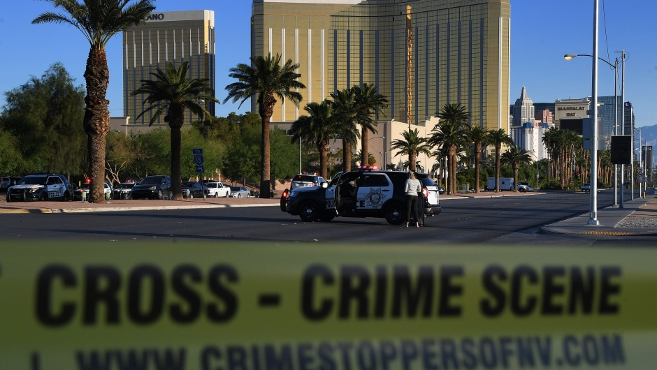 Crime scene tape surrounds the Mandalay Hotel (background) after a gunman killed at least 50 people and wounded more than 200 others when he opened fire on a country music concert in Las Vegas, Nevada on October 2, 2017. Police said the gunman, a 64-year-old local resident named as Stephen Paddock, had been killed after a SWAT team responded to reports of multiple gunfire from the 32nd floor of the Mandalay Bay, a hotel-casino next to the concert venue. / AFP PHOTO / Mark RALSTON (Photo credit should read MARK RALSTON/AFP/Getty Images)