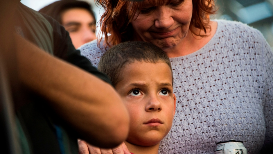 Nine-year old Alexander Wells is hugged by his grandmother at a candlelight vigil at Las Vegas City Hall October 2, 2017, after a gunman killed at least 58 people and wounded more than 500 others when he opened fire on a country music concert in Las Vegas, Nevada late October 1, 2017. Alexander had friends who were injured in another shooting recently and insisted on attending this vigil according to his family. / AFP PHOTO / Robyn Beck (Photo credit should read ROBYN BECK/AFP/Getty Images)