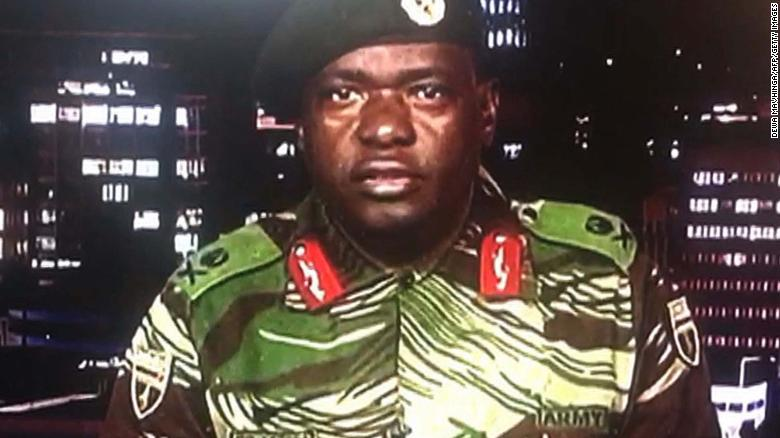 "TOPSHOT - This screen grab taken early on November 15, 2017 from a television broadcast on the Zimbabwe Broadcasting corporation (ZBC) shows Zimbabwe Major General Sibusiso Moyo reading a statement at the ZBC broadcast studio in Harare. Zimbabwe's military appeared to be in control of the country on November 15 as generals denied staging a coup but used state television to vow to target ""criminals"" close to President Robert Mugabe. / AFP PHOTO / Dewa MAVHINGA (Photo credit should read DEWA MAVHINGA/AFP/Getty Images)"