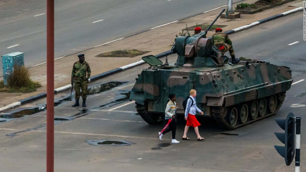 """Young women walk past an armoured personnel carrier that stations by an intersection as Zimbabwean soldiers regulate traffic in Harare on November 15, 2017. Zimbabwe's military appeared to be in control of the country on November 15 as generals denied staging a coup but used state television to vow to target """"criminals"""" close to President Mugabe. / AFP PHOTO / Jekesai NJIKIZANA (Photo credit should read JEKESAI NJIKIZANA/AFP/Getty Images)"""