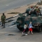 "Young women walk past an armoured personnel carrier that stations by an intersection as Zimbabwean soldiers regulate traffic in Harare on November 15, 2017. Zimbabwe's military appeared to be in control of the country on November 15 as generals denied staging a coup but used state television to vow to target ""criminals"" close to President Mugabe. / AFP PHOTO / Jekesai NJIKIZANA (Photo credit should read JEKESAI NJIKIZANA/AFP/Getty Images)"