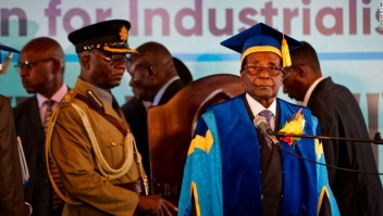 Zimbabwe's President Robert Mugabe, center-right, arrives to preside over a student graduation ceremony at Zimbabwe Open University on the outskirts of Harare, Zimbabwe Friday, Nov. 17, 2017. Mugabe is making his first public appearance since the military put him under house arrest earlier this week. (AP Photo/Ben Curtis)