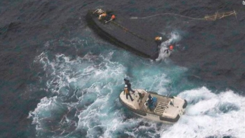 In this Wednesday, Nov. 15, 2017, photo provided by the 9th Regional Japan Coast Guard Headquarters, a boat of the Japan Coast Guard approaches a capsized wooden vessel, top, for a rescue operation in the water off Noto peninsula, northern coast of Japan. Three crew members rescued from the capsized boat are North Koreans, and Tokyo is arranging their return home. The area is a rich fishing ground where poachers from North Korea and China have been spotted. (9th Regional Japan Coast Guard Headquarters via AP)