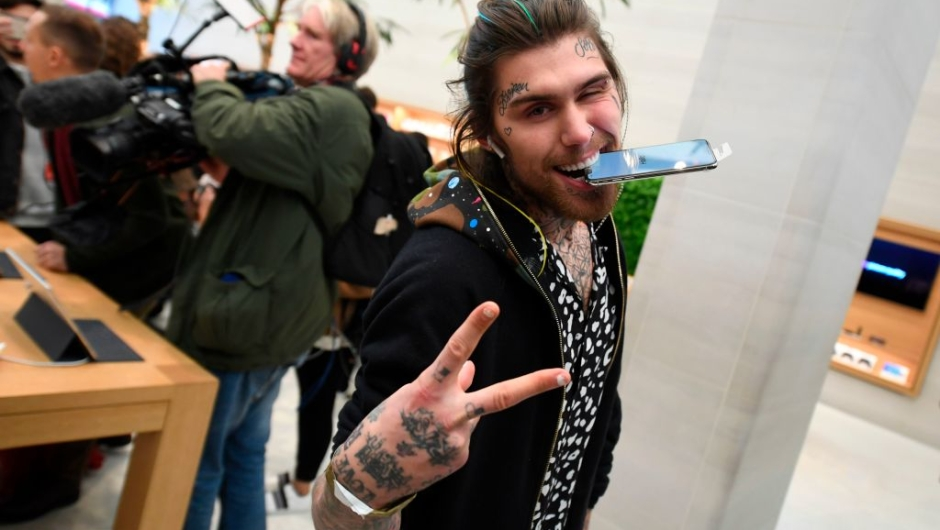Marco White Jr., son of British chef Marco Pierre White poses with his Apple iPhone X after being one of the first to purchase the newly released smartphone at Apple's Regent Street store in central London on November 3, 2017. Apple's flagship iPhone X hit stores on November 3, as the world's most valuable company predicted bumper sales despite the handset's eye-watering price tag and celebrated a surge in profits. The device features facial recognition, cordless charging and an edge-to-edge screen made of organic light-emitting diodes used in high-end televisions. It marks the 10th anniversary of the first iPhone release and is released in about 50 markets around the world. / AFP PHOTO / Chris J Ratcliffe (Photo credit should read CHRIS J RATCLIFFE/AFP/Getty Images)