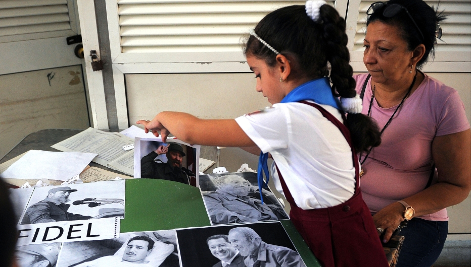 A Cuban primary school student works on a collage with images of late Cuban leader Fidel Castro in Havana, on November 23, 2017. Cuba commemorates on November 25 the first anniversary of the death of Fidel Castro, focused on an electoral process that will imply a presidential change, in a framework of economic regression, hostility from the United States, and stagnation in its reforms. / AFP PHOTO / YAMIL LAGE (Photo credit should read YAMIL LAGE/AFP/Getty Images)