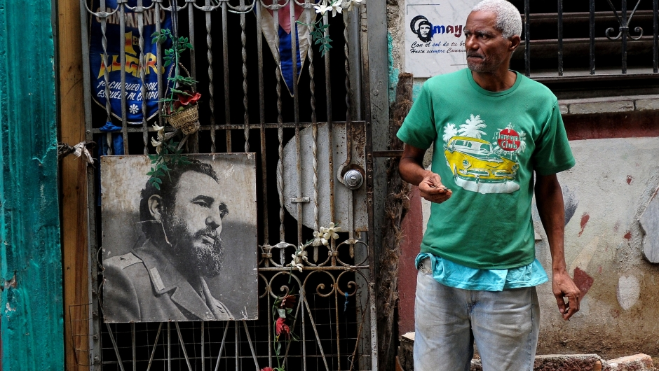 A man stands next to a poster of late Cuban leader Fidel Castro in Havana, on November 24, 2017. Cuba commemorates on November 25 the first anniversary of the death of Fidel Castro, focused on an electoral process that will imply a presidential change, in a framework of economic regression, hostility from the United States, and stagnation in its reforms. / AFP PHOTO / YAMIL LAGE (Photo credit should read YAMIL LAGE/AFP/Getty Images)