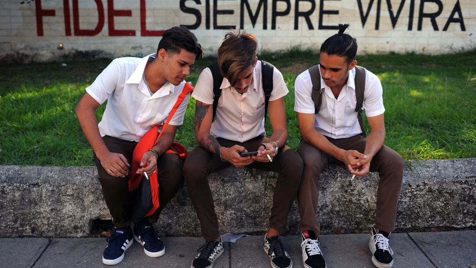 """Cuban youngsters look at a cellphone as they sit in front of a graffiti reading """"Fidel (Castro) will always live"""" in Havana on November 24, 2017. Cuba commemorates on November 25 the first anniversary of the death of Fidel Castro, focused on an electoral process that will imply a presidential change, in a framework of economic regression, hostility from the United States, and stagnation in its reforms. / AFP PHOTO / YAMIL LAGE (Photo credit should read YAMIL LAGE/AFP/Getty Images)"""