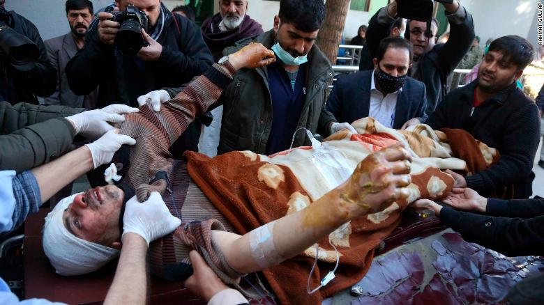 People carry an injured man into the hospital after a suicide attack in Kabul, Afghanistan, Thursday, Dec. 28, 2017. Authorities say two simultaneous attacks in Afghanistan's capital have left dozens dead. (AP Photo/Rahmat Gul)