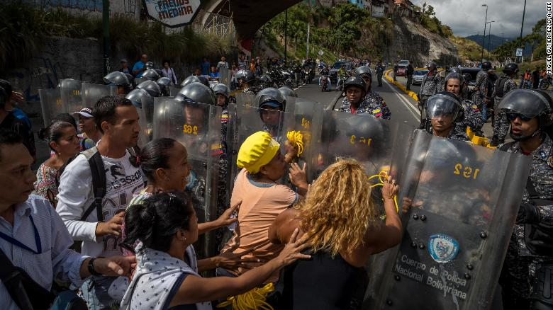 epa06408476 A group of people protest in front of members of the Bolivarian National Police (PNB) in Caracas, Venezuela, 28 December 2017. The protests over the shortage, the scarcity of food and the lack of domestic gas and water continued today in Caracas and other cities of the country, according to local media information. EPA-EFE/MIGUEL GUTI???RREZ