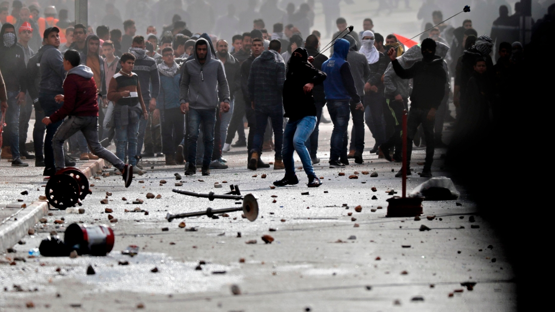 protestors clash with Israeli forces near an Israeli checkpoint in the West Bank city of Bethelem on December 7, 2017. US President Donald Trump's recognition of Jerusalem as Israel's capital sparked a Palestinian general strike and a call for a new intifada as fears grew of fresh bloodshed in the region. / AFP PHOTO / THOMAS COEX