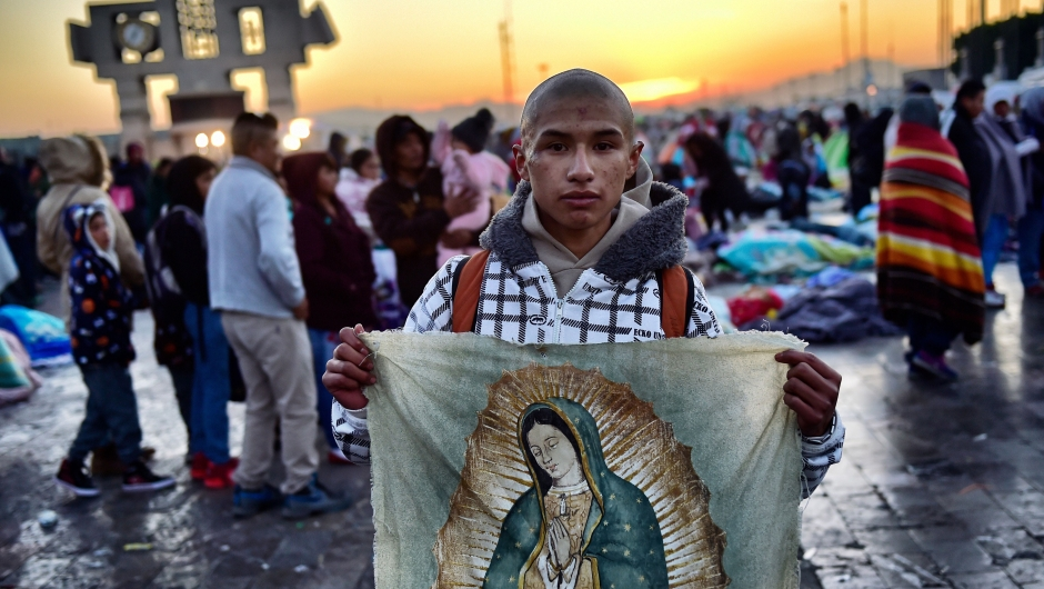 A Catholic faithful holds a banner with an image of the Virgin of Guadalupe during a procession as part of the feast of the virgin, patron saint of Mexico, in Mexico City on December 12, 2017. Millions of pilgrims visit Mexico City's Guadalupe Basilica to honour the country's patron saint, the Virgin of Guadalupe. / AFP PHOTO / Pedro PARDO (Photo credit should read PEDRO PARDO/AFP/Getty Images)