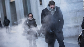 NEW YORK, NY - JANUARY 07: A man clenches his fists while walking past a steam vent on the morning of January 7, 2014 in New York, United States. A polar vortex has descended on much of North America, coming down from the Arctic, bringing record freezing temperatures across much of the country. (Photo by Andrew Burton/Getty Images)