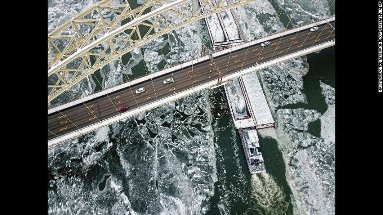 A barge cuts through ice on the Ohio River as it passes under the West End Bridge, along the North Shore district in Pittsburgh on Monday, Jan. 1, 2018. (Haley Nelson/Pittsburgh Post-Gazette via AP)
