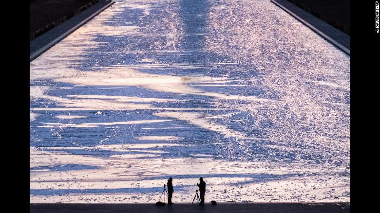 Two photographers are silhouetted against the frozen surface of the Reflecting Pool on the National Mall in Washington as they capture the first sunrise of the new year, Monday, Jan. 1, 2018. (AP Photo/J. David Ake)