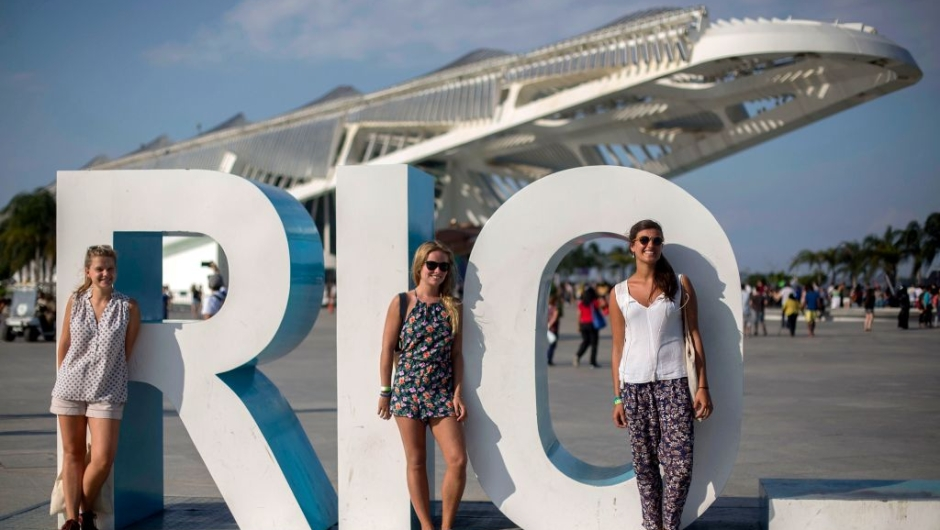 ourists pose to photos with the Museum of Tomorrow on the background in Rio de Janeiro, Brazil, on September 19, 2017. / AFP PHOTO / Mauro PIMENTEL (Photo credit should read MAURO PIMENTEL/AFP/Getty Images)