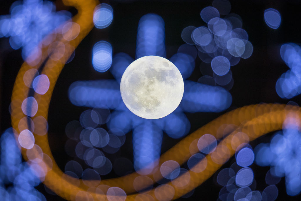 "WELLS, ENGLAND - JANUARY 01: The first full moon of 2018 rises behind festive seasonal lights on display in the High Street in Wells on January 1, 2018 in Somerset, England. Tonight's full moon, which is known by Native American tribes as the ""Wolf Moon"", is also a supermoon which means it coincides with the Moon's closest approach to Earth, known as the perigee. Tonights Wolf Moon is the first of two full moons in January. The second will take place on the night of January 31 and in some areas of the world this will also happen at the same time as a total lunar eclipse. (Photo by Matt Cardy/Getty Images)"