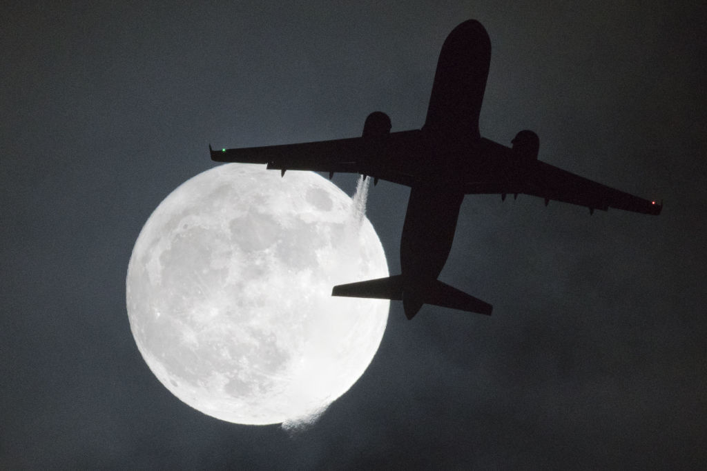 "TOPSHOT - A plane flys in front of a ""super moon"" or ""wolf moon"" on its approach to London Heathrow Airport on January 1, 2018. / AFP PHOTO / Justin TALLIS (Photo credit should read JUSTIN TALLIS/AFP/Getty Images)"