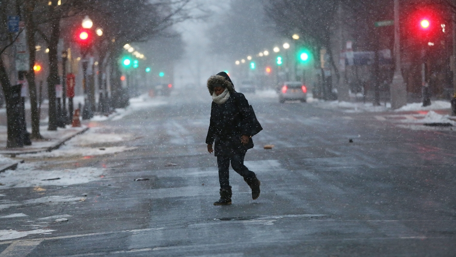BOSTON, MA - JANUARY 04: People walk through the empty streets of Boston as the snow begins to fall during a massive winter storm on January 4, 2018 in Boston, United States. Schools and businesses throughout the Boston area are closed as the city is expecting over a foot of snow and blizzard like conditions throughout the day. (Photo by Spencer Platt/Getty Images)