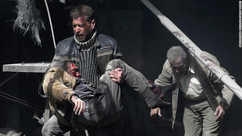 Un hombre lleva a una víctima herida entre edificios en ruinas.