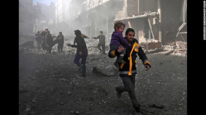 Un hombre lleva a un niño que rescató de los escombros en Hamouria.