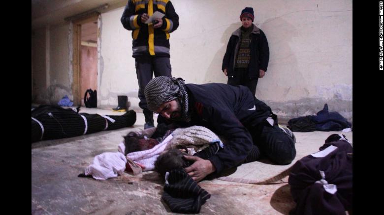 Un hombre llora sobre su hijo, que murió en los ataques aéreos de Mesraba.