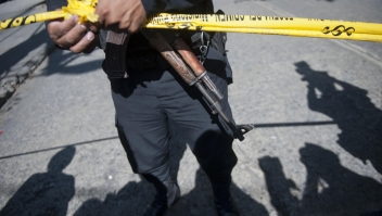 A policeman stands guard at the crime scene after Francisco Palomo, an attorney Guatemala's former dictator Efrain Rios Montt, was shot dead in Guatemala City on June 3, 2015. Palomo was driving in his car when gunmen unloaded a hail of bullets, striking him at least 12 times, and killing him in broad daylight in a busy commercial area of Guatemala City, said firefighters spokesman Raul Hernandez. AFP PHOTO Johan ORDONEZ (Photo credit should read JOHAN ORDONEZ/AFP/Getty Images)
