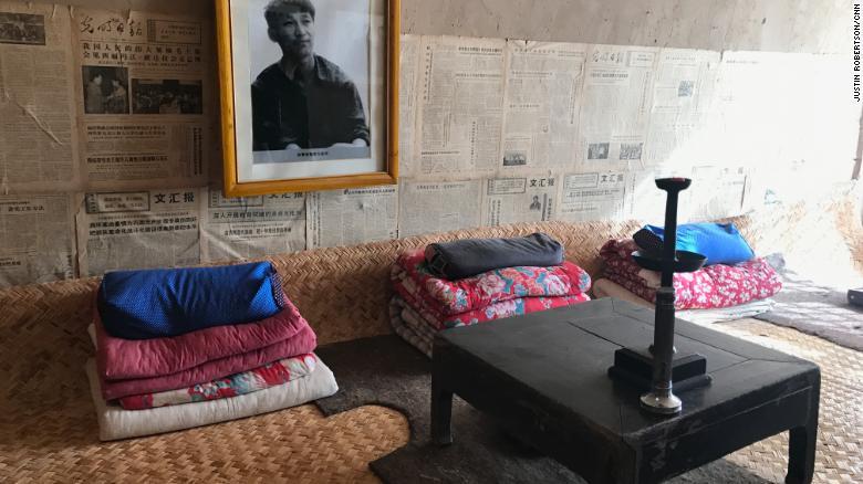 """Una foto de un Xi juvenil, así como viejos periódicos, adornan la pared sobre su antigua cama compartida en una """"casa cueva""""."""