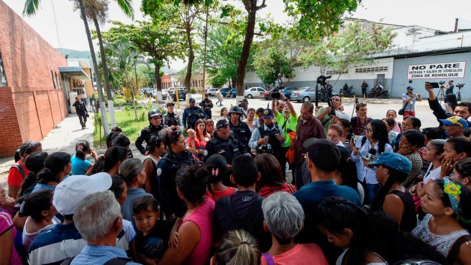 Policías informan a familiares tras el incendio que acabó con la vida de al menos 68 personas en Venezuela. (Crédito: UAN BARRETO/AFP/Getty Images)