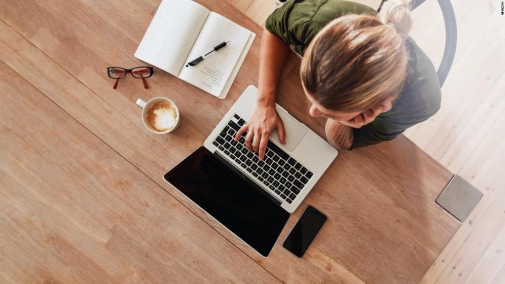 Una mujer con un laptop y un café