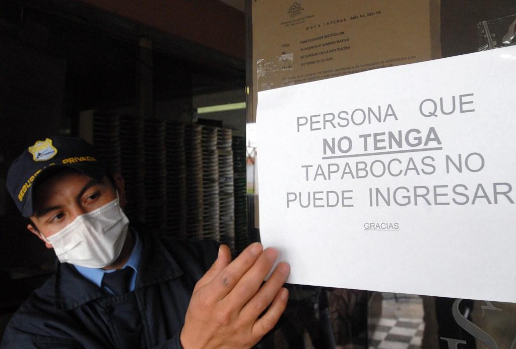 Un miembro de seguridad muestra uno de los carteles que se colgaron en Colombia por la crisis del AH1N1 en 2009. Foto de archivo. (Crédito: LUIS RAMIREZ/AFP/Getty Images)