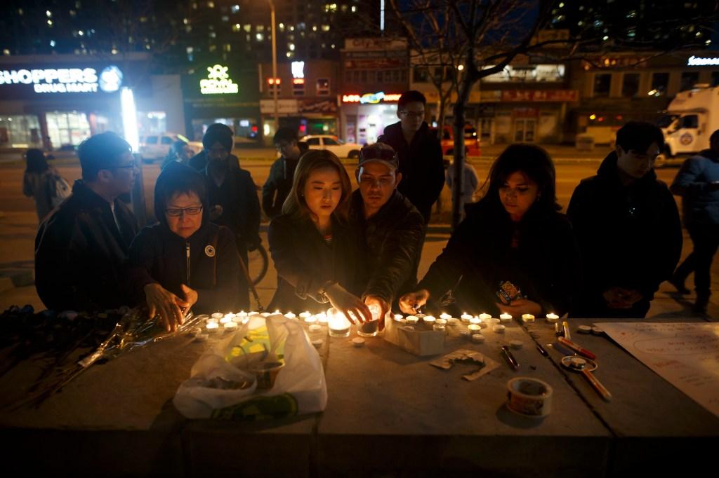 Personas dejan velas y mensajes en el lugar en el que tuvo lugar un atropello masivo que dejó varios muertos en Toronto (Canadá) durante la noche del 23 de abril de 2018. (Crédito: Cole Burston/Getty Images)