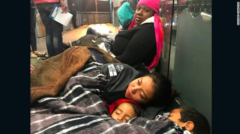 Las inmigrantes Tesla Rich (sentada) y Gabriela Hernández con sus hijos Jonathan y Omar, esperan juntas para que les permitan entrar en el puesto fronterizo.