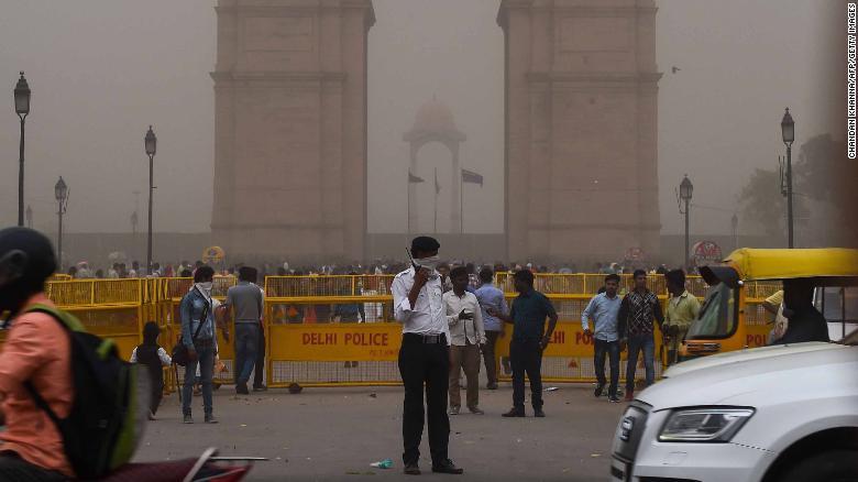 Un policía de tráfico indio se cubre la cara mientras se encuentra de servicio durante una tormenta de polvo en Nueva Delhi el 2 de mayo. (Crédito: CHANDAN KHANNA/AFP/Getty Images)