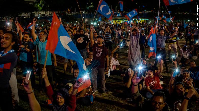 Los partidarios de Mahathir Mohamad animan mientras miran televisión en vivo el anuncio de resultados en Kuala Lumpur.