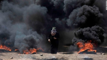 A Palestinian woman walks through black smoke from burning tires during a protest on the Gaza Strip's border with Israel, Monday, May 14, 2018. Thousands of Palestinians are protesting near Gaza's border with Israel, as Israel prepared for the festive inauguration of a new U.S. Embassy in contested Jerusalem. (AP Photo/Khalil Hamra)