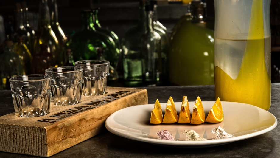 Espadin mezcal with cuish (a variety of agave) served with a dish with orange slices and three different flavors of sea salt - hibiscus, penny royal mint and agave worm - at the Zandunga restaurant which offers traditional Tehuantepec Isthmus cuisine in Oaxaca, Mexico on March 1, 2017. / AFP PHOTO / Omar TORRES (Photo credit should read OMAR TORRES/AFP/Getty Images)