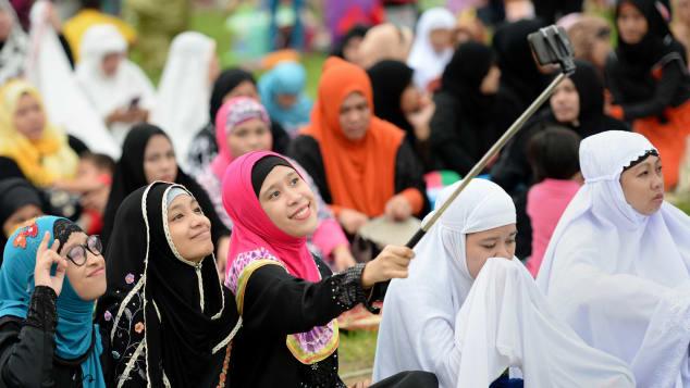"""Jóvenes musulmanes toman una """"selfie"""" antes de las oraciones del viernes para marcar el final del Ramadán el año pasado en Manila, Filipinas. (Crédito: TED ALJIBE/AFP/Getty Images)"""