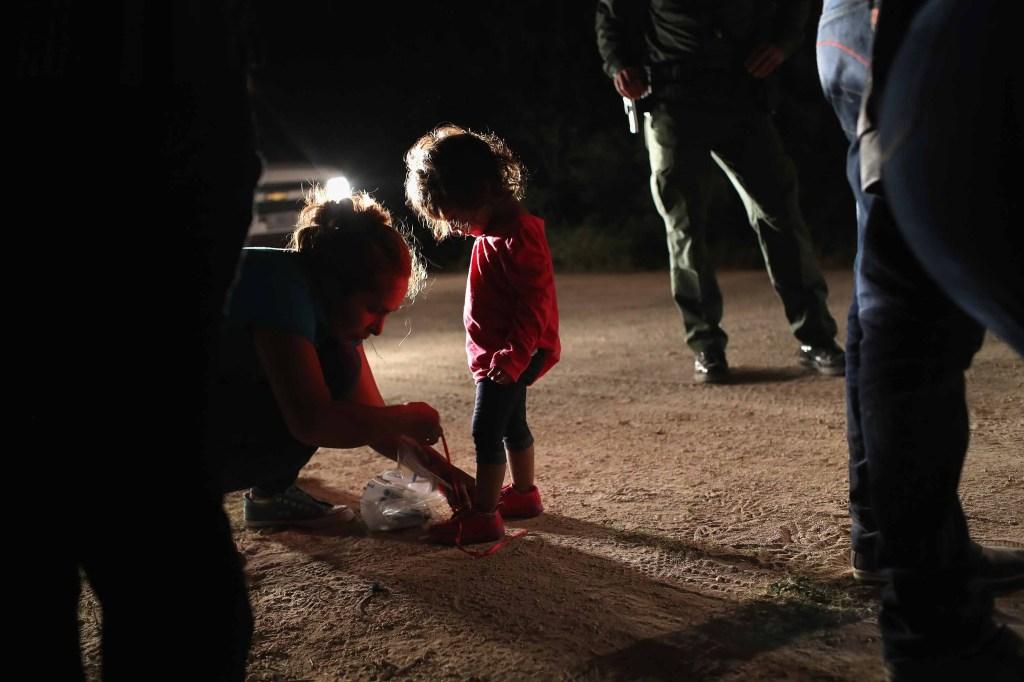 La madre de la niña quita los cordones de sus zapatos, según le pidieron los agentes fronterizos. (Crédito: John Moore/Getty Images)