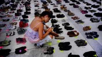 Una mujer coloca uno de los cientos de zapatos en memoria de los fallecidos por el huracán María frente al Capitolio de Puerto Rico, en San Juan, el viernes 1 de junio de 2018. (Crédito: AP Photo/Ramon Espinosa)