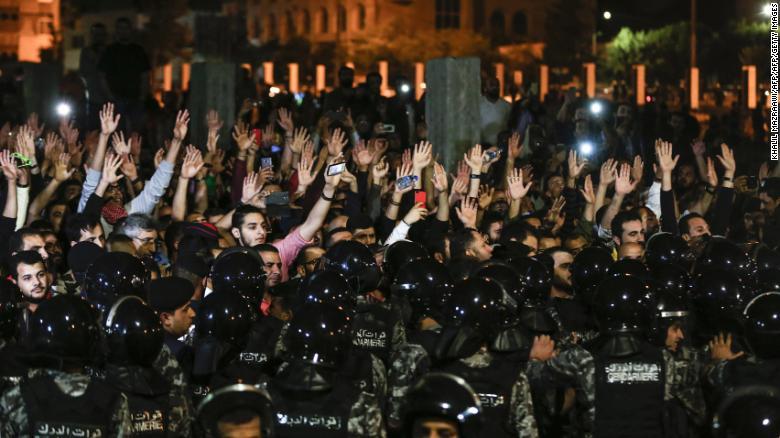 Manifestantes jordanos levantan sus manos en protestas frente a la oficina del primer ministro. (Crédito: KHALIL MAZRAAWI/AFP/Getty Images)