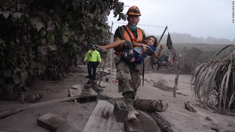 epa06784018 A Guatemalan rescue team worker carries a girl in El Rodeo, Escuintla, Guatemala, 03 June 2018, after the eruption at Fuego volcano, which has left at least 25 dead, around 20 injured and more than 1.7 million people were affected. EPA-EFE/NOE PEREZ