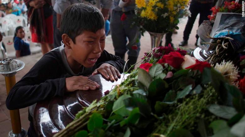 A youth cries over the coffin of Nery Otoniel Gomez Rivas, 17, whose body was pulled from the volcanic ash during the eruption of the Volcan de Fuego, which in Spanish means Volcano of Fire, during his wake at the main park of the town San Juan Alotenango, Guatemala, Monday, June 4, 2018. A fiery volcanic eruption in south-central Guatemala sent lava flowing into rural communities, killing dozens as rescuers struggled to reach people where homes and roads were charred and blanketed with ash. (AP Photo/Luis Soto)