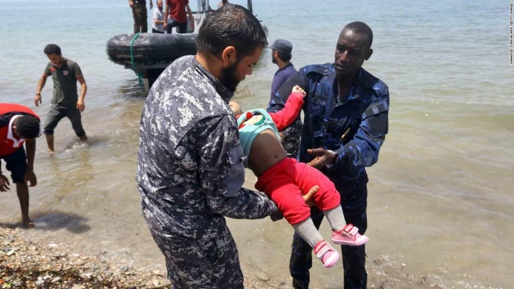 Sobrevivientes llegan a la costa mientras dos hombres toman a otro de los bebés. (Crédito: MAHMUD TURKIA/AFP/Getty Images)